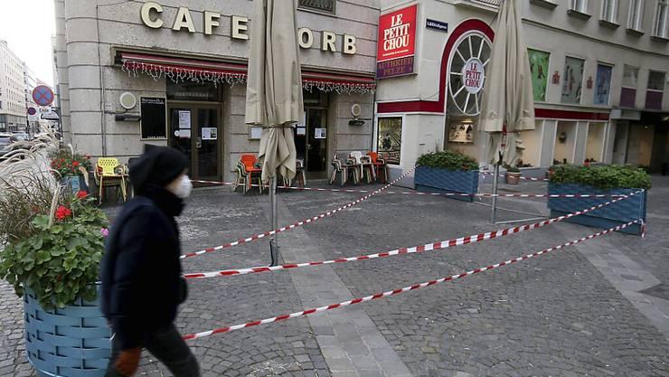 Ein Mann mit Mund-Nasen-Schutz geht an einem geschlossenen Cafe in der Innenstadt vorbei. (Symbolbild) Foto: Ronald Zak/AP/dpa