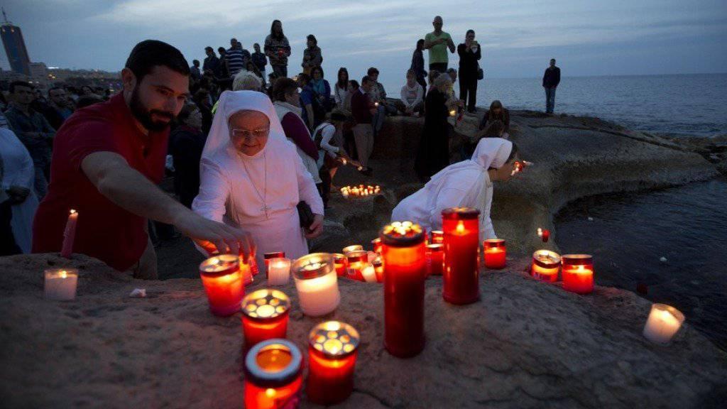 Menschen entzünden an der Küste von Malta Kerzen für die Opfer des im April 2015 vor der libyschen Küste gesunkenen Schiffes. (Archiv)