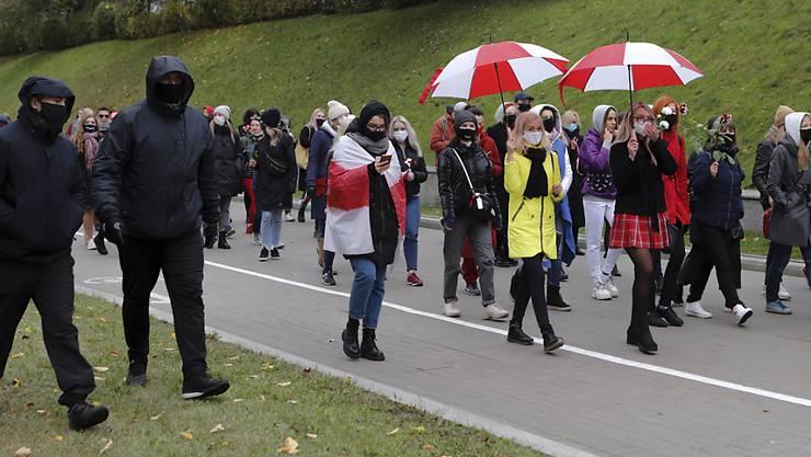 Polizisten in Zivil begeiten belarussische Frauen mit Mund-Nasen-Schutz bei einem Protest der Opposition in Minsk. Foto: Uncredited/AP/dpa