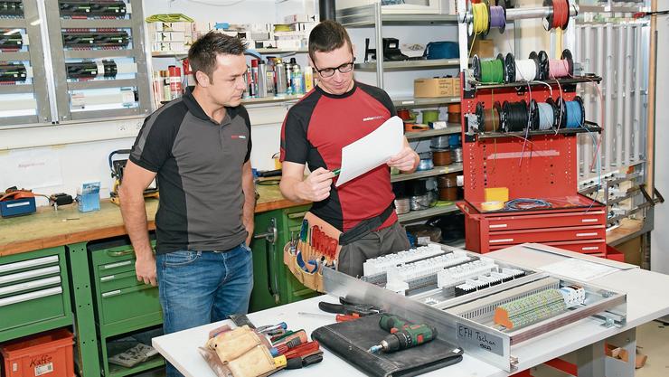 Pascal Bösiger (rechts) mit Arbeitgeber Kurt Meier bei der Arbeit in der Firma Elektro Meier in Bettwil.