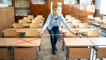 Ist der Abstand gross genug? Eine Lehrerin misst ein Schulzimmer aus.
