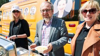 CVP-Risotto am 1. Mai in Schöftland: Oliver Hunziker mit Isabell Landolfo – beide auf der Nationalratsliste – beim Schöpfen. Vom orangen Bus lächelt Ständeratskandidatin Marianne Binder, die später noch vorbeikam.