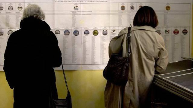 Zwei Frauen bereiten sich am Sonntag in einem Wahlbüro in Rom auf die Stimmabgabe vor (Archiv)