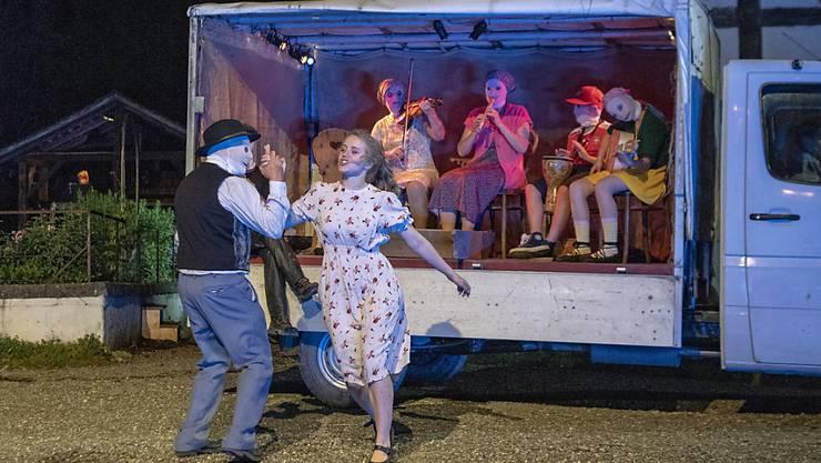 Ein Spielmann mit Maske tanzt mit Vreneli - die Musikanten fahren auf dem Ballenberg ganz modern per Lieferwagen auf.