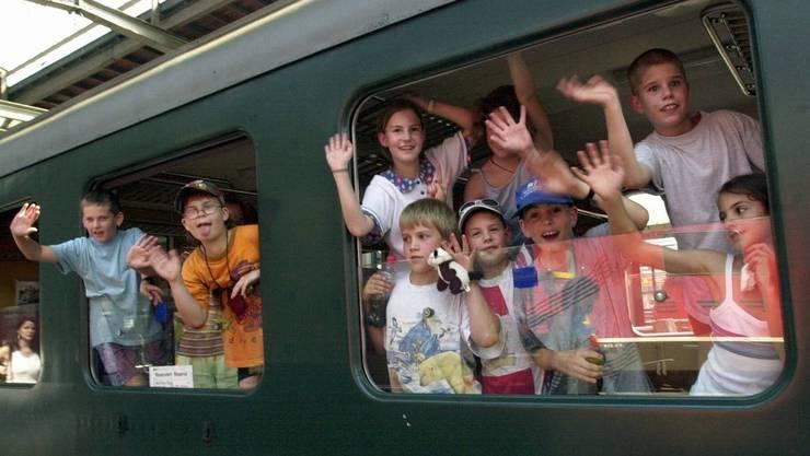 Kinder winken aus einem Zug.