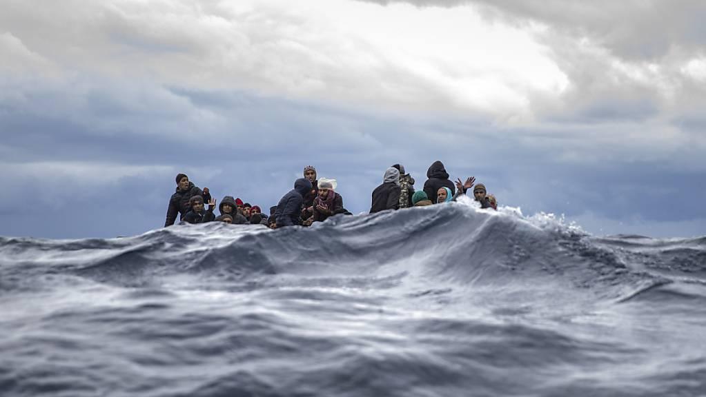Männer aus Marokko und Bangladesch sitzen in einem überfüllten Holzboot im Mittelmeer vor der Küste von Libyen. (Archiv)