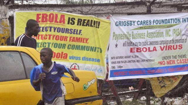Menschen in Monrovia vor Transparenten mit Ebola-Warnungen