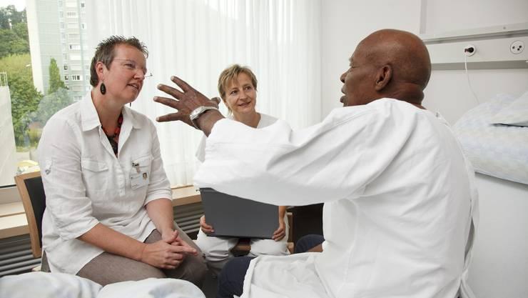 Szene aus dem Kantonsspital Olten: Dolmetscherin Gina Kunst (links), ein Patient aus Somalia und Birgitt Virgolini besprechen mit dem Patienten den Spitalaustritt und weiteren Therapieverlauf.