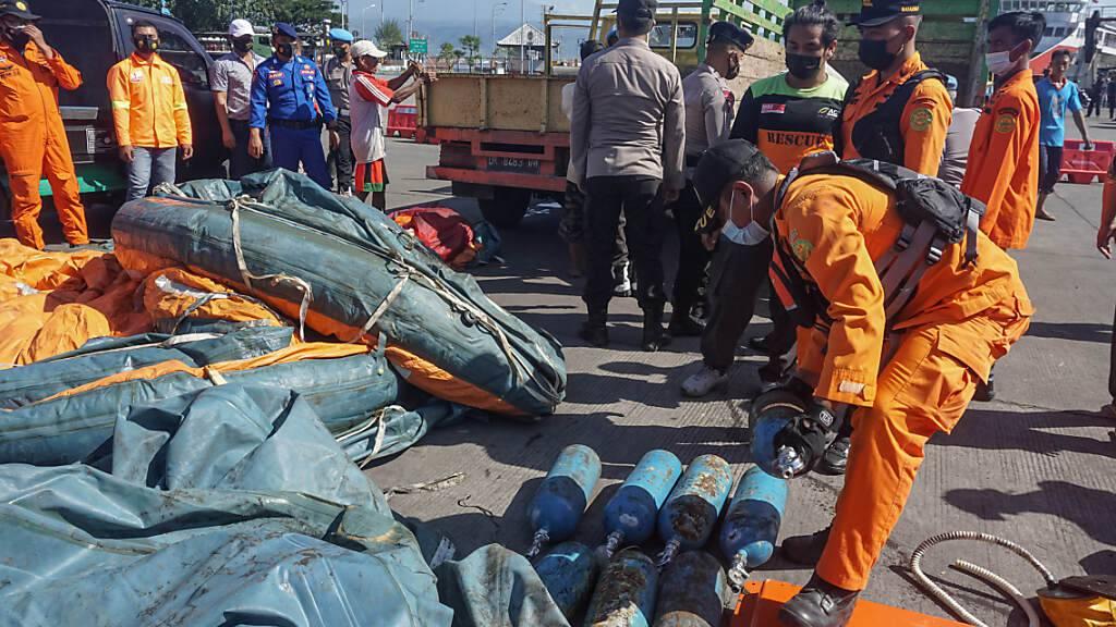 Mitglieder des Bali National Search and Rescue Board (Basarnas Bali) sammeln Rettungswesten und Teile der gekenterten Fähre KM Yunice ein. Bei einem Fährunglück vor der Küste der indonesischen Insel Bali sind mindestens sieben Menschen ums Leben gekommen. Foto: Dicky Bisinglasi/ZUMA Wire/dpa Foto: Dicky Bisinglasi/ZUMA Wire/dpa