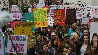 Polinnen und Polen halten vor dem Parlamentsgebäude in Warschau Plakate in die Luft: Sie zeigen ihren Unmut über ein mögliches komplettes Verbot von Abtreibungen.