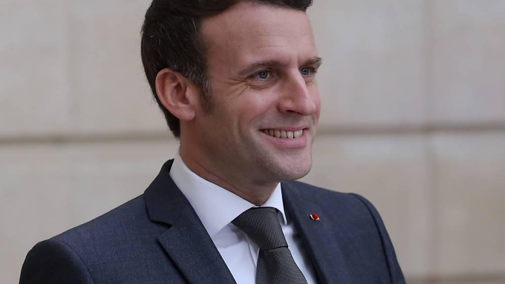 Emmanuel Macron, Präsident von Frankreich, lächelt während einer per Videoübertragung gemeinsamen Pressekonferenz mit Bundeskanzlerin Merkel. Foto: Thibault Camus/AP/dpa