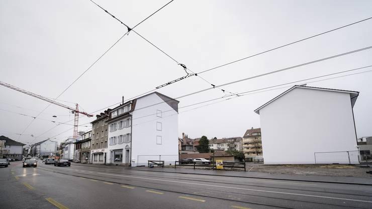 Die Brache, links daneben die Liegenschaften Hauptstrasse 12 (weisse Fassade) und 14: Vom Gebäude 14 her müsste die Parzelle für Autos erschlossen werden. Keine einfache Aufgabe.