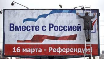 Ein Mann befestigt in Sewastopol eine Wahlwerbung für die Abstimmung: «Zusammen mit Russland! Abstimmung 16. März.»