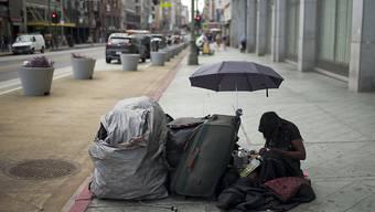 Eine obdachlose Frau auf einem Trottoir in Los Angeles mit ihren Habseligkeiten