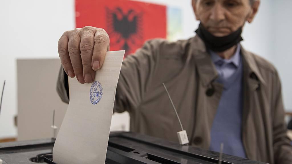 Eine Mann wirft seinen Stimmzettel in eine Wahlurne. Rund 3,6 Millionen Bürger sind dazu aufgerufen, ihre Stimme bei der Parlamentswahl in Albanien abzugeben. Foto: Visar Kryeziu/AP/dpa