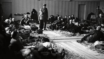 Robert Narev (Bildmitte) mit einem Soldaten nach der Ankunft im Hadwig-Schulhaus im Februar 1945. Die Turnhalle wurde damals als Strohlager für jüdische Flüchtlinge hergerichtet.
