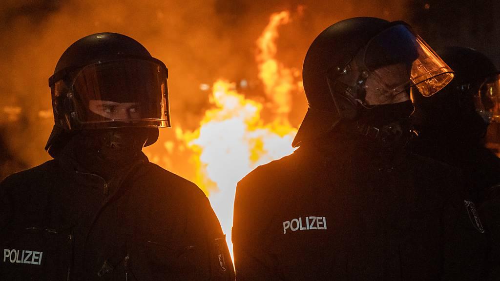 Polizisten stehen vor einem Feuer am Rande des Demonstrationszug linker und linksradikaler Gruppen unter dem Motto «Demonstration zum revolutionären 1. Mai». Foto: Christophe Gateau/dpa