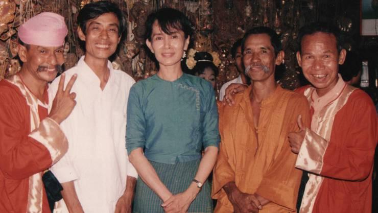 Die Moustache Brothers 2002 mit Friedensnobelpreisträgerin Aung San Suu Kyi und einem Marionettenbauer – v.l. Pa Pa Lay, Ko Ko Naing (der zweite Bruder von Lu Maw), Suu Kyi, Lu Maw und Lu Zaw.