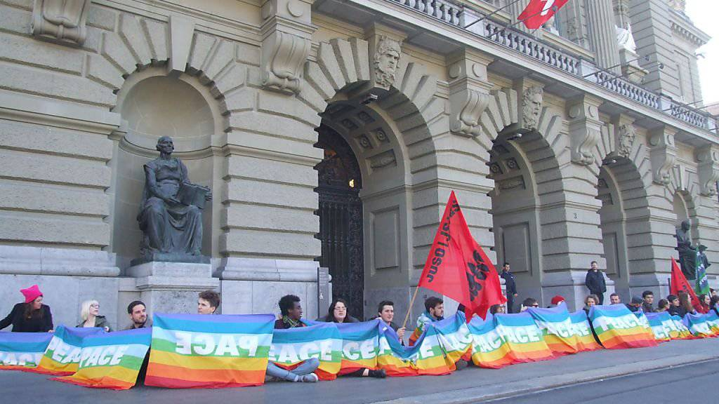 Aktivistinnen und Aktivisten bildeten eine Menschenkette vor dem Bundeshaus und forderten damit das Parlament auf, sich für eine konsequente Friedenspolitik einzusetzen.