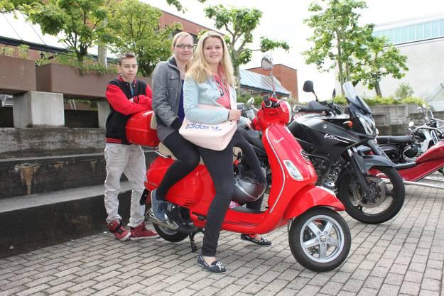 Fabienne Beck, Jeanine Schmid und Marco Schmid (von rechts) mischen mit ihrer roten Vespa das Motorradtreffen auf