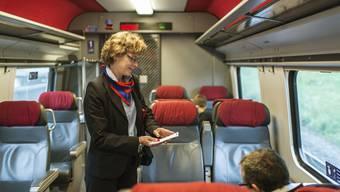 Eine SBB-Zugbegleiterin konrtolliert im 1. Klasse-Wagen des ICN von Zuerich nach Genf Billette.