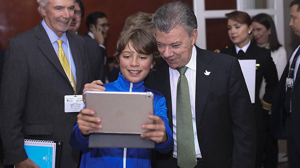 Kolumbiens Präsident Juan Manuel Santos stellt sich einem Jungen für ein Selfie zur Verfügung (Archiv)