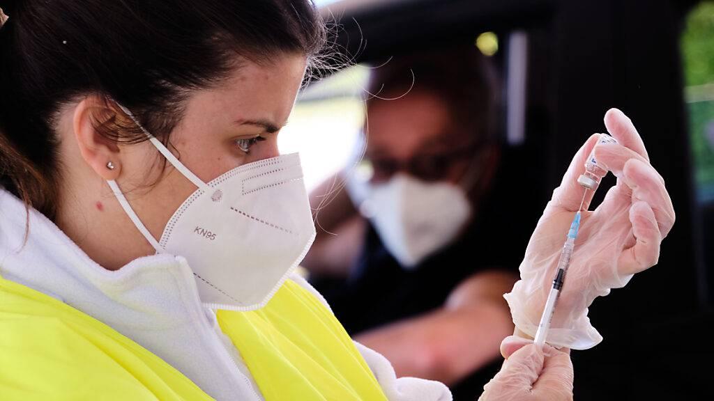 Eine Mitarbeiterin des Gesundheitswesens zieht in einem Drive-In-Impfzentrum am Outlet-Center von Valmonte eine Spritze mit einem Corona-Impfstoff auf. Foto: Mauro Scrobogna/LaPresse via ZUMA Press/dpa