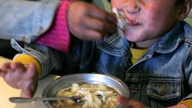 Ein Strassenkind in der Mongolei erhält sein Essen
