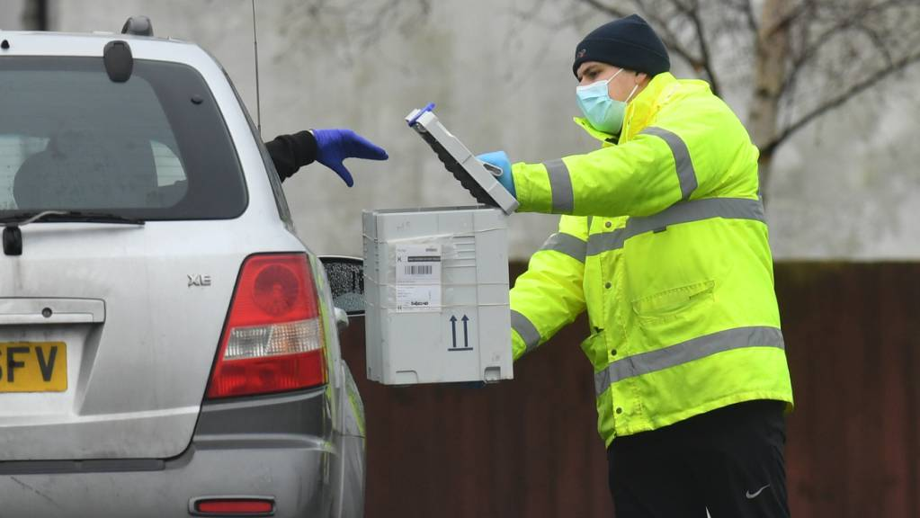 In einem Corona-Testzentrum wirft ein Fahrer aus dem Auto ein Testkit in eine Box. Die Bürger in England sollen sich bald zweimal pro Woche kostenlos auf das Coronavirus testen lassen können.