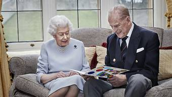 HANDOUT - Dieses am 19. November zur Verfügung gestellte Foto zeigt die britische Königin Elizabeth II. und Prinz Philip, Herzog von Edinburgh, die eine selbstgemachte Karte zum 73. Hochzeitstag betrachten, die ihnen zuvor von ihren Urenkeln überreicht wurde. Foto: Chris Jackson/Pool via Getty/AP/dpa - ACHTUNG: Nur zur redaktionellen Verwendung im Zusammenhang mit der aktuellen Berichterstattung und nur mit vollständiger Nennung des vorstehenden Credits