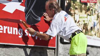 Ein Mitarbeiter der APG klebt ein Plakat zur SVP-Einwanderungsinitiative auf eine Werbetafel in St. Moritz (Archiv)
