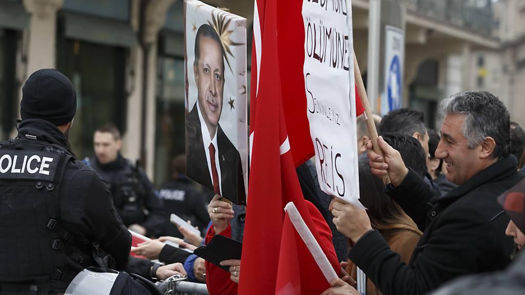 Ein Anhänger hält ein Porträt des türkischen Präsidenten Recep Tayyip Erdogan vor dem Genfer Hotel in die Höhe, wo der türkische Präsident einen Tag vor der Eröffnung des globalen Flüchtlingsforums des UNHCR erwartet wurde.