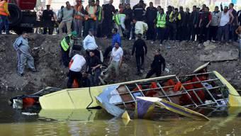 Rettungskräfte ziehen den verunglückten Bus aus dem Kanal in Kairo