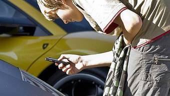 Ein Teenager fotografiert mit seinem Handy das Logo eines Lamborghini (Archiv)