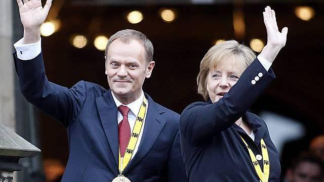 Tusk und Merkel (rechts) winken nach der Zeremonie den Menschen zu