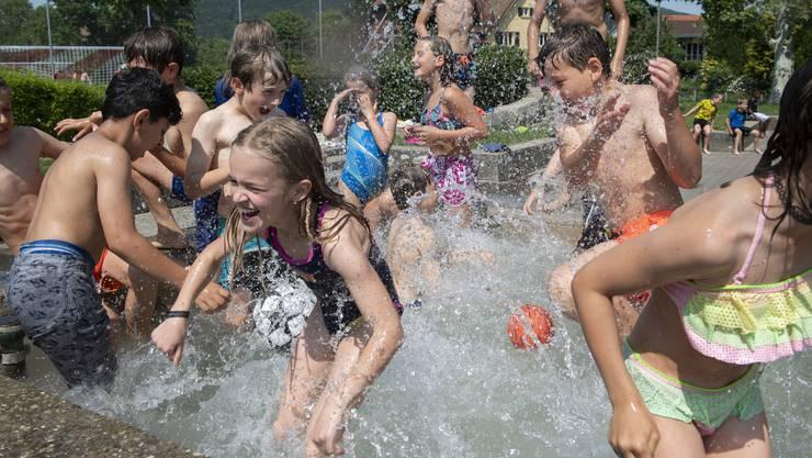 Auch sie gönnen sich eine Abkühlung: Eine Schulklasse vom Schulhaus Stock in Küttigen kühlt sich im Brunnen auf dem Pausenplatz ab.