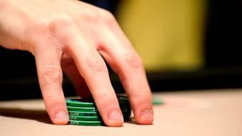 Ein Pokerspieler hält seine Spielchips in seiner Hand