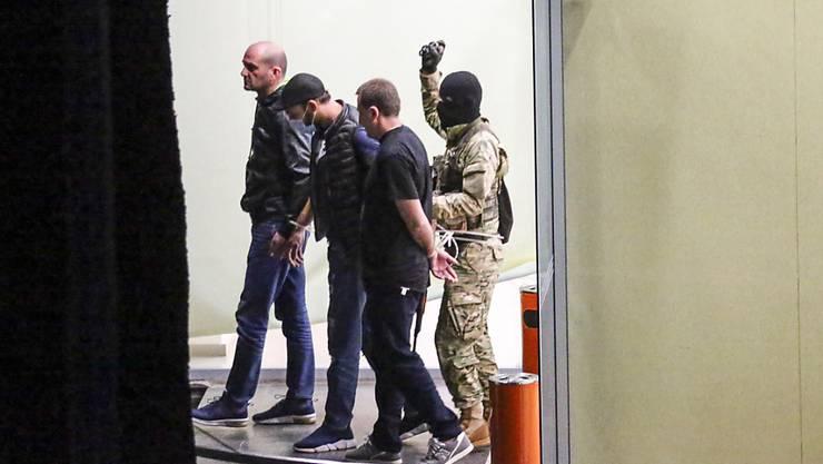 dpatopbilder - Ein Geiselnehmer (r) mit einer Waffe und einer Handgranate in der Hand läuft hinter drei mit Kabelbindern gefesselten Polizisten, die er als Geiseln genommen hat, aus einem Bankgebäude in Westgeorgien. Der bewaffnete Mann forderte eine halbe Millionen US-Dollar Lösegeld. Foto: Zurab Tsertsvadze/AP/dpa