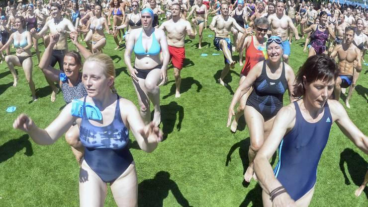 Die Teilnehmer waermen sich ein und turnen vor dem den Start der Seeueberquerung 2015 am Mythenquai