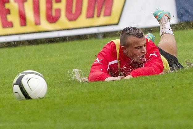 Auch ihm ist es passiert: Xherdan Shaqiri fliegt im verregneten Training hin.