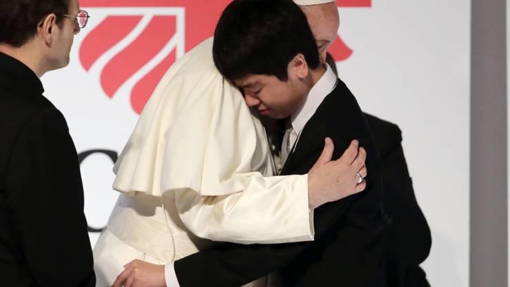 Papst Franziskus umarmt bei seinem Besuch in Tokio ein Opfer der Nuklearkatastrophe von Fuskushima im Jahr 2011.