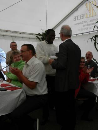 Gemeindepräsident Martin Blaser übergibt Bischof Godfrey Makumbi aus Uganda ein Geschenk