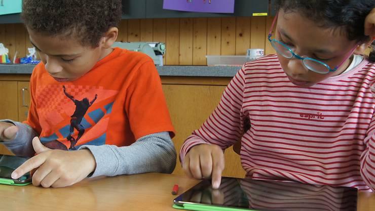 Fleissig üben die Kinder, auf dem iPad einzelne Buchstaben zu schreiben – danach bringen sie das Gelernte zu Papier.