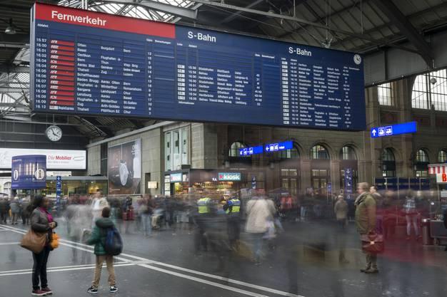 Die mechanische Fallblattanzeige umgeben von Reisenden am Hauptbahnhof in Zuerich