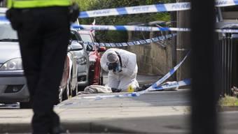 Polizisten und Kriminalbeamte sichern den Tatort in Birstall, einer Ortschaft in der Nähe von Leeds.