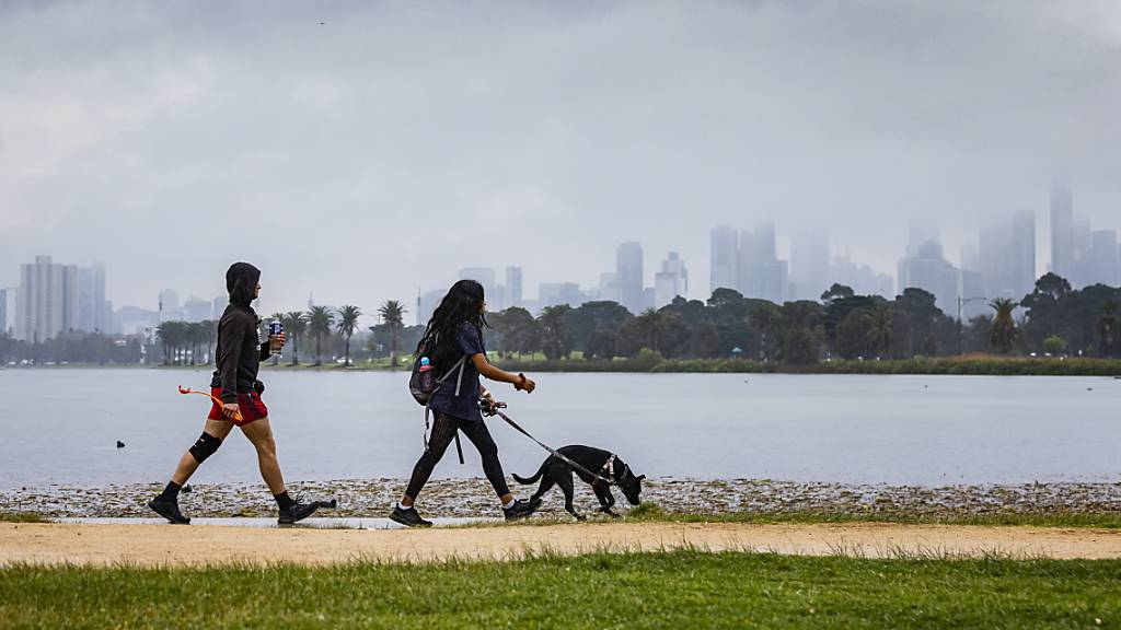 People are seen walking a dog at Albert Park Lake in Melbourne, Thursday, September 30, 2021. Melbourne's lockdown will remain in place until 70 per cent of Victorians aged over 16 are double-vaccinated, which is forecast for October 26. (AAP Image/Daniel Pockett) NO ARCHIVING