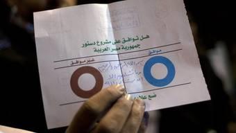 Ein ägyptischer Wahlhelfer zeigt einen ungültigen Wahlzettel
