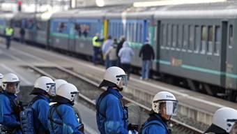 Polizisten bewachen am Bahnhof Zürich-Altstetten einen Zug mit FC-Basel-Fans. (Archivbild)