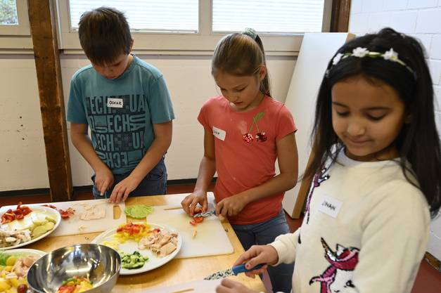 12 Kinder bereiten zusammen mit Tamara Moser und Melanie Stoller ihr Mittagessen vor.