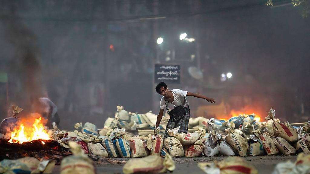 Ein Demonstrant stapelt Säcke auf einer Straße in Yangon. Foto: Theint Mon Soe/SOPA Images via ZUMA Wire/dpa